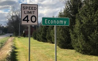 A speed limit sign is seen beside a city sign for Economy, Indiana, U.S., November 10, 2020. Picture taken November 10, 2020. REUTERS/Timothy Aeppel