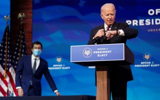 U.S. President-elect Joe Biden looks at his watch as former South Bend, Indiana Mayor Pete Buttigieg arrives behind him to be announced as his nominee for secretary of transportation during a news conference at Biden's transition headquarters in Wilmington, Delaware, U.S., December 16, 2020. REUTERS/Kevin Lamarque/Pool     TPX IMAGES OF THE DAY