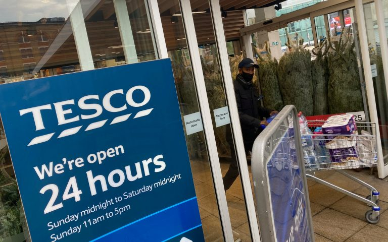 A shopper wearing a protective face-mask passes christmas trees for sale and a sign indicating 24 hour opening times at a Tesco supermarket amid the spread of the coronavirus disease (COVID-19), London, Britain, December 6, 2020. REUTERS/Toby Melville