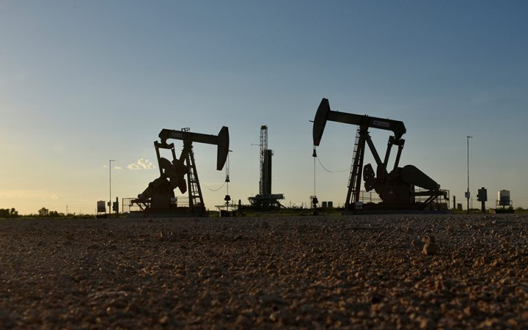 FILE PHOTO: FILE PHOTO: Pump jacks operate in front of a drilling rig in an oil field in Midland, Texas U.S. August 22, 2018. REUTERS/Nick Oxford/File Photo/File Photo
