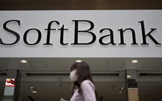 ** HOLD FOR FUTURE USE ** In this Oct. 8, 2019 photo, a person walks by a SoftBank shop in Tokyo. (AP Photo/Eugene Hoshiko)