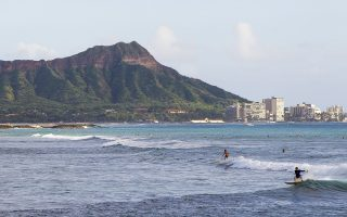 FILE - In this Nov. 4, 2014 file photo, surfers ride waves off Ala Moana Beach Park in Honolulu, with Diamond Head mountain in the background. The Hawaii Tourism Authority says the number of travelers to the islands increased 4.3 percent in October compared to the same month last year, setting a record for the month. (AP Photo/Marco Garcia, File)